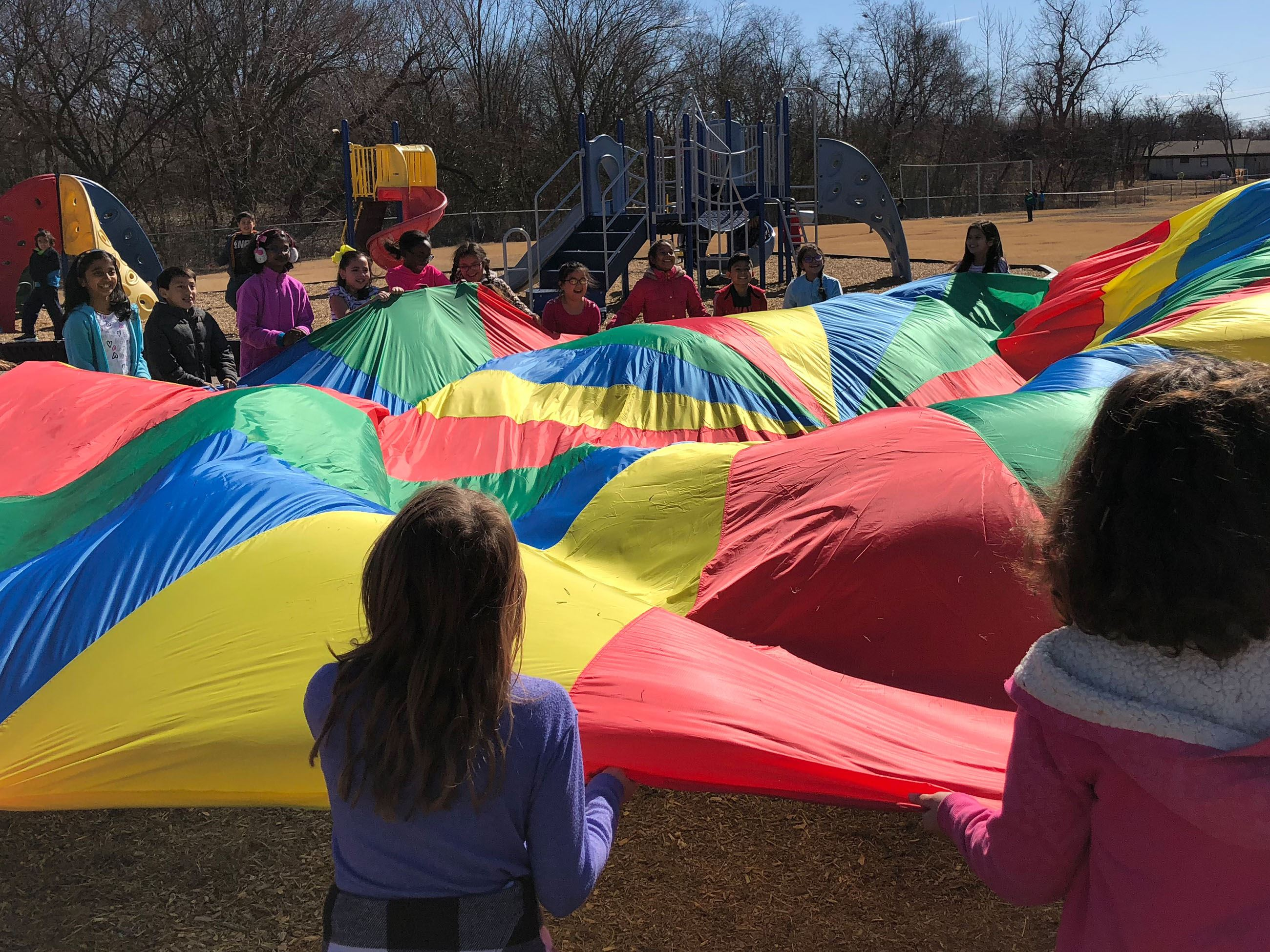 Kids playing with a colorful parachute
