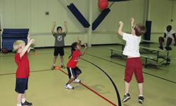 Kids playing basketball in a gymnasium